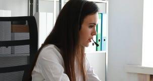 Vrouw die op hoofdtelefoon spreken en laptop in modern bureau met behulp van stock footage