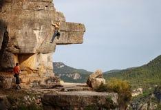 Vrouw die op klip, het mannelijke partner vastmaken beklimmen royalty-vrije stock afbeeldingen