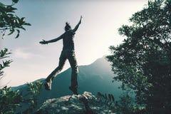 Vrouw die op klippen` s rand springen Stock Fotografie
