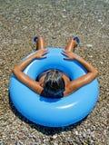 Vrouw die op kust van overzees in een opblaasbare doughnut zonnebaden Royalty-vrije Stock Foto's