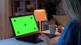 Vrouw die op laptop met het groene scherm thuis gebruiken stock videobeelden