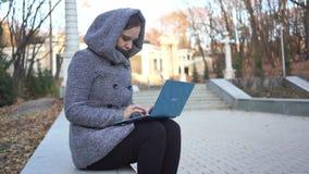 Vrouw die op laptop op parkbank schrijven stock video