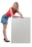 Vrouw die op leeg teken leunt Stock Foto's