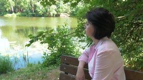 Vrouw die op middelbare leeftijd dichtbij de vijver, die op een bank rusten zitten stock videobeelden