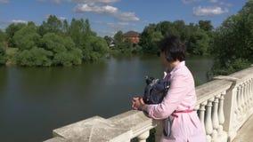 Vrouw die op middelbare leeftijd dichtbij de vijver, die op een traliewerk rusten leunen stock videobeelden