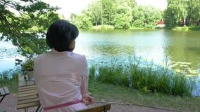 Vrouw die op middelbare leeftijd dichtbij de vijver rusten, die bij een lijst zitten stock video