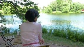 Vrouw die op middelbare leeftijd dichtbij de vijver rusten, die bij een lijst zitten stock footage