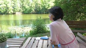 Vrouw die op middelbare leeftijd dichtbij de vijver rusten, die bij een lijst zitten stock videobeelden