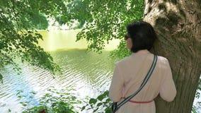 Vrouw die op middelbare leeftijd dichtbij een vijver rusten, die tegen een boom leunen stock videobeelden