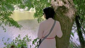 Vrouw die op middelbare leeftijd dichtbij een vijver rusten, die tegen een boom leunen stock footage
