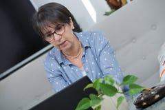 Vrouw die op middelbare leeftijd laptop thuis met behulp van stock foto