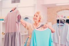 Vrouw die op middelbare leeftijd onder twee kleding in de boutique kiezen royalty-vrije stock fotografie