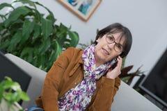 Vrouw die op middelbare leeftijd op telefoon thuis spreken royalty-vrije stock afbeeldingen