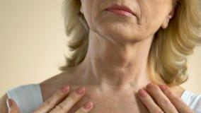 Vrouw die op middelbare leeftijd zorgvuldig gerimpelde huid van haar hals en borst onderzoeken stock video