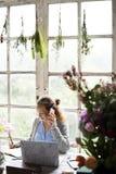Vrouw die op Mobiele Telefoon in Bloemwinkel spreken royalty-vrije stock fotografie