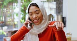 Vrouw die op mobiele telefoon in cafetaria 4k spreken stock footage