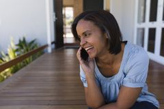 Vrouw die op mobiele telefoon op de portiek thuis spreken royalty-vrije stock fotografie