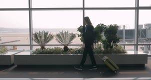 Vrouw die op mobiele telefoon in luchthaventerminal babbelen stock videobeelden