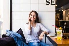 Vrouw die op mobiele telefoon met vriend spreken terwijl het zitten alleen in moderne koffiewinkel stock afbeeldingen