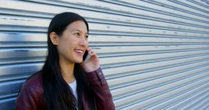 Vrouw die op mobiele telefoon spreken terwijl het hebben van een koffie op straten 4k stock videobeelden