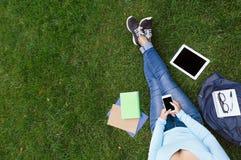 Vrouw die op mobiele zitting op het groene gras babbelen royalty-vrije stock foto