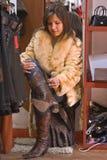 Vrouw die op nieuwe laarzen probeert Royalty-vrije Stock Afbeeldingen
