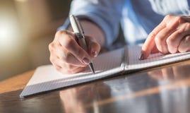 Vrouw die op notitieboekje schrijft stock fotografie