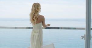 Vrouw die op Oceaanfront balcony railing leunen stock video