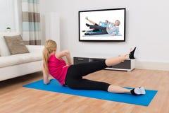 Vrouw die op Oefening Mat In Front Of Television uitoefenen Stock Afbeeldingen