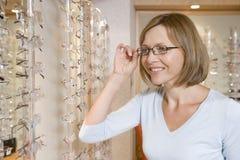 Vrouw die op oogglazen bij optometristen probeert Royalty-vrije Stock Foto