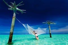 Vrouw die op over-waterhangmat leunt Royalty-vrije Stock Afbeeldingen