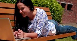 Vrouw die op parkbank liggen die laptop met behulp van stock video