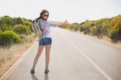 Vrouw die op plattelandsweg liften Royalty-vrije Stock Afbeelding