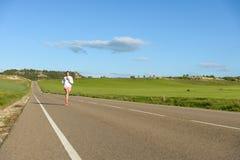 Vrouw die op plattelandsweg lopen Stock Foto