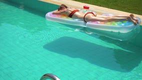 Vrouw die op poolvlotter in de zomerdag liggen stock videobeelden