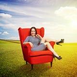 Vrouw die op rode stoel rusten Stock Foto's