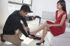 Vrouw die op schoenen bij manieropslag proberen Stock Foto's