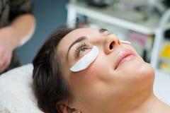 Vrouw die op schoonheidsbehandeling met helft-cirkel stootkussens onder ogen wachten stock afbeelding