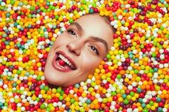 Vrouw die op snoepjes liggen Stock Foto's