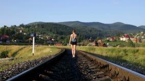 Vrouw die op spoorweg in bergen lopen stock footage