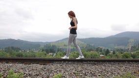 Vrouw die op spoorweg in bergen lopen stock videobeelden