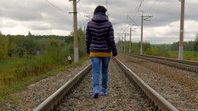Vrouw die op spoorwegsporen lopen stock footage