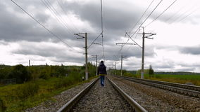 Vrouw die op spoorwegsporen lopen stock videobeelden