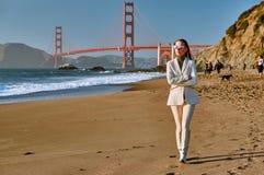 Vrouw die op strand dichtbij Golden gate bridge lopen royalty-vrije stock afbeelding