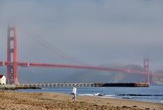 Vrouw die op strand dichtbij Golden gate bridge lopen stock afbeelding