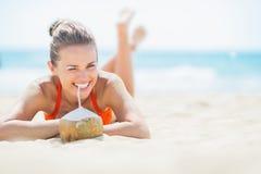 Vrouw die op strand en het drinken kokosmelk leggen Stock Foto's