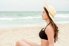 Vrouw die op strand haar hoofdtelefoons luisteren Stock Foto's
