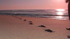 Vrouw die op strand lopen die voetdrukken verlaten stock video