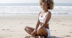 Vrouw die op strand in lotusbloempositie mediteren stock footage