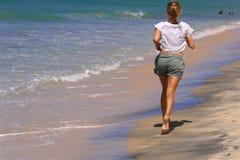 Vrouw die op strand in ochtend lopen Royalty-vrije Stock Fotografie